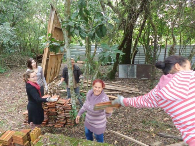 As meninas organizam as telhas que são tiradas de construção a ser demolida...