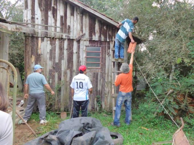 ... enquanto outra parte do grupo retira as telhas.